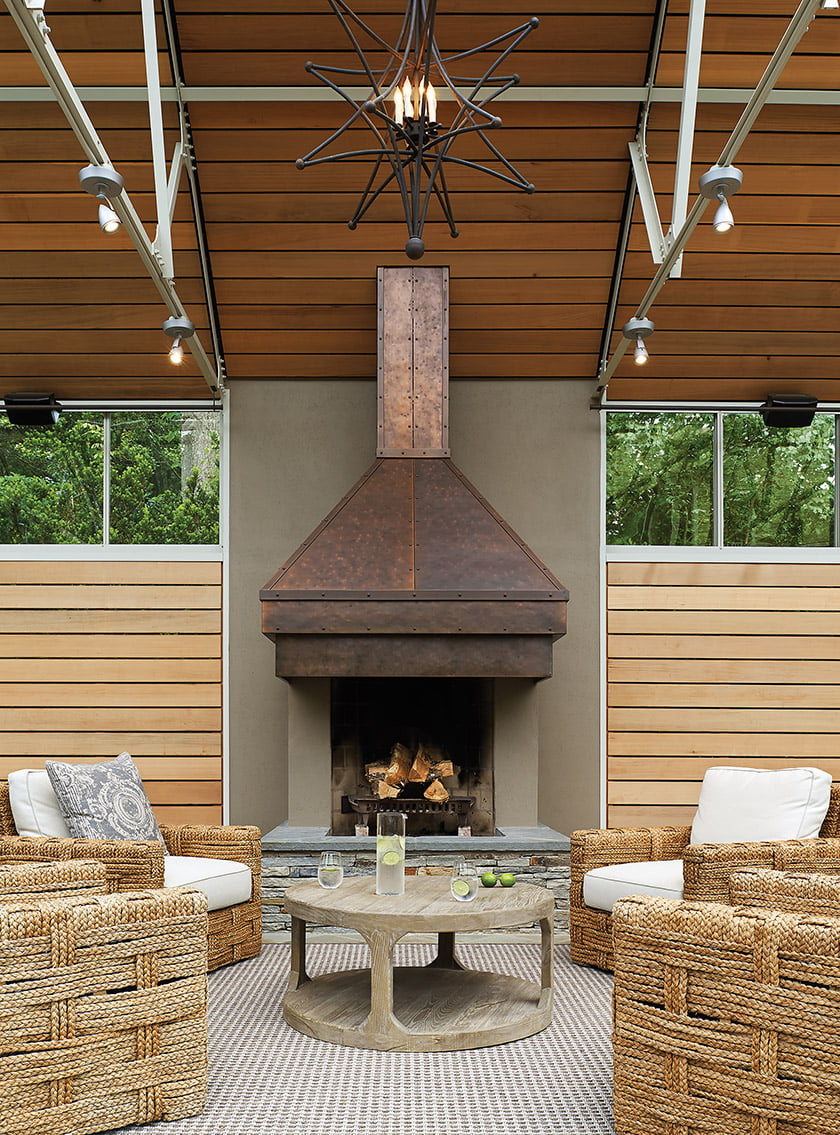 The front entry aligns with the fireplace, made of stucco with a burnished-copper hood and a stacked-stone hearth.