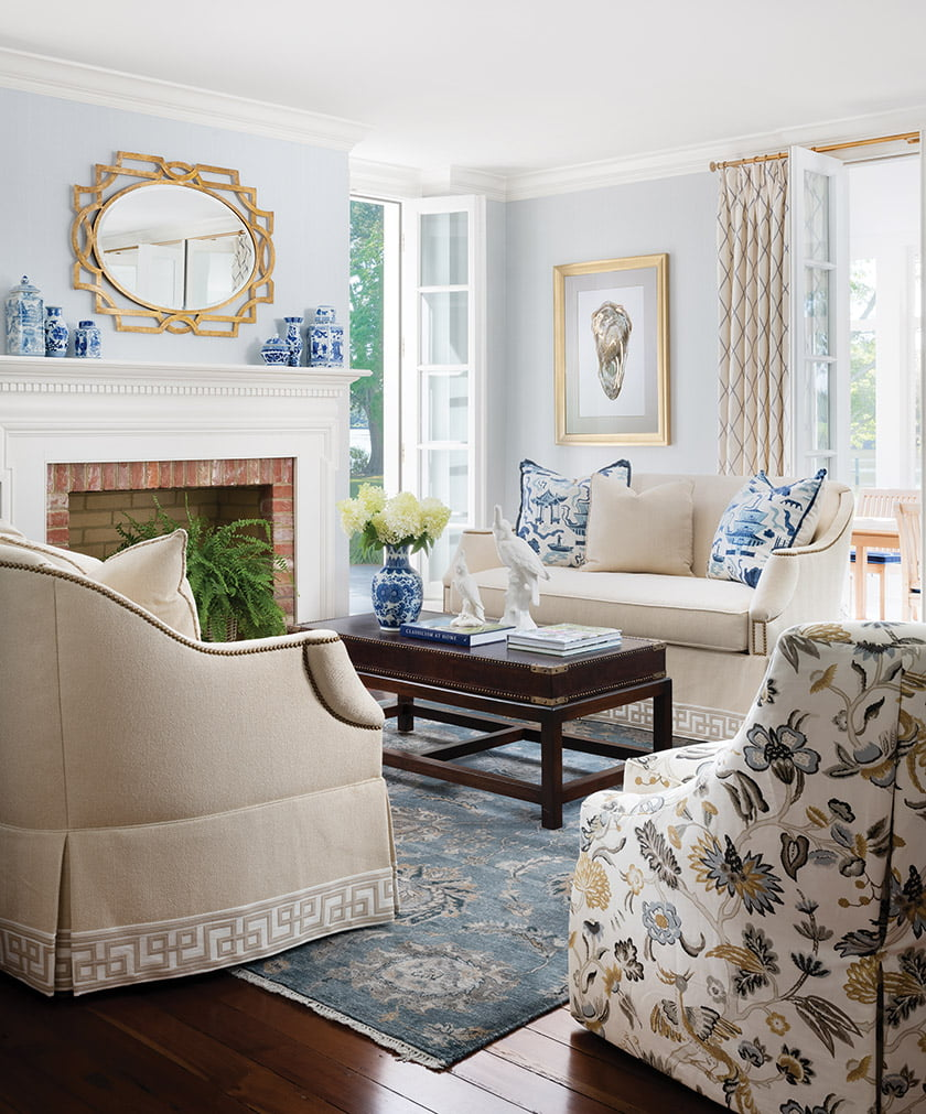 A Loloi rug grounds the living room, where vintage loveseats sit beside Wesley Hall chairs.