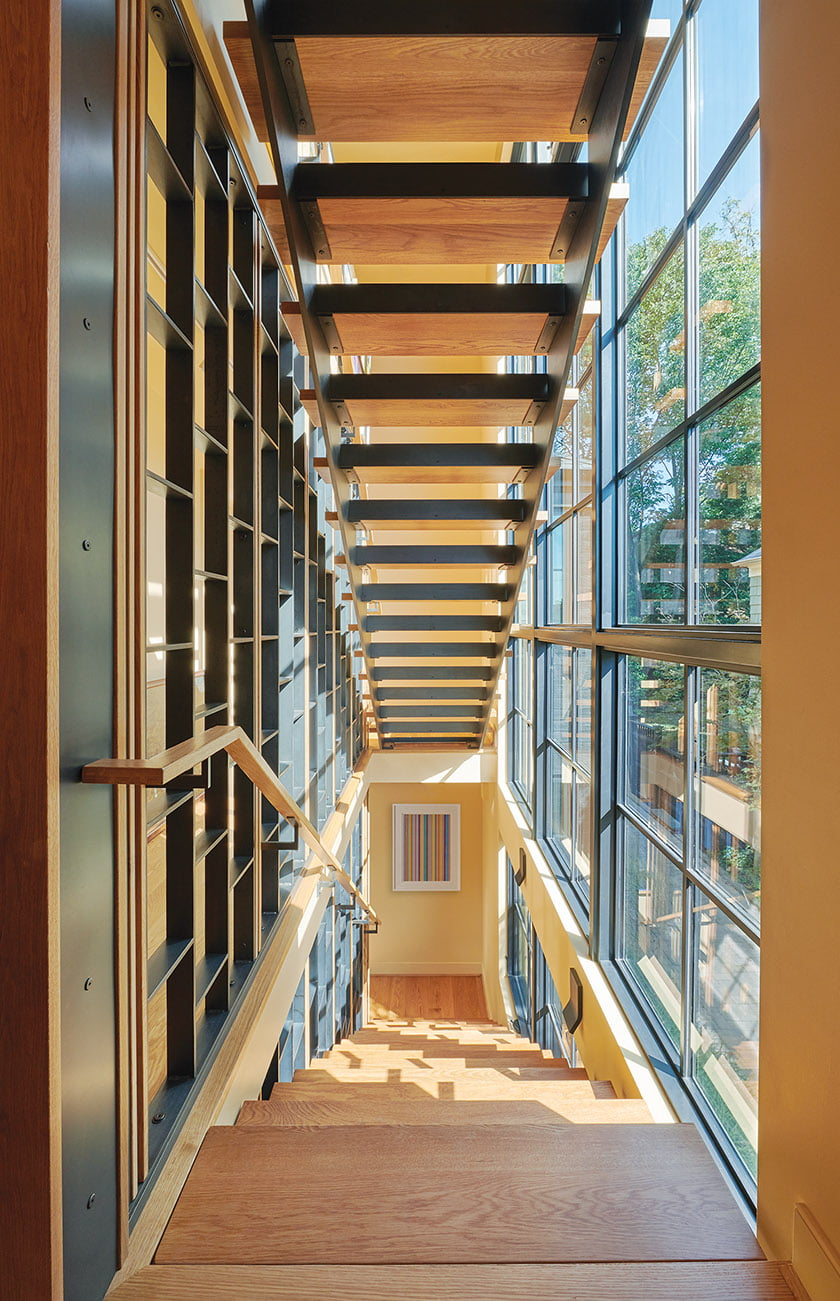 The staircase is bathed in light by three stories of windows.