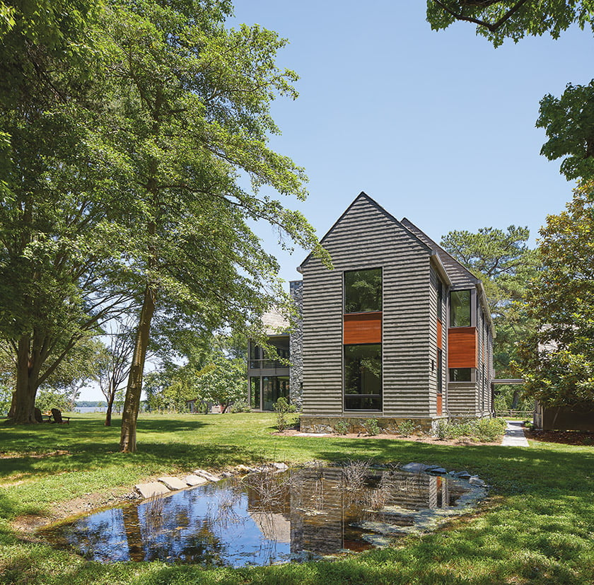 At its far end, the home's bark-gray, shingled 'L' boasts woodland views and a modified rain garden.