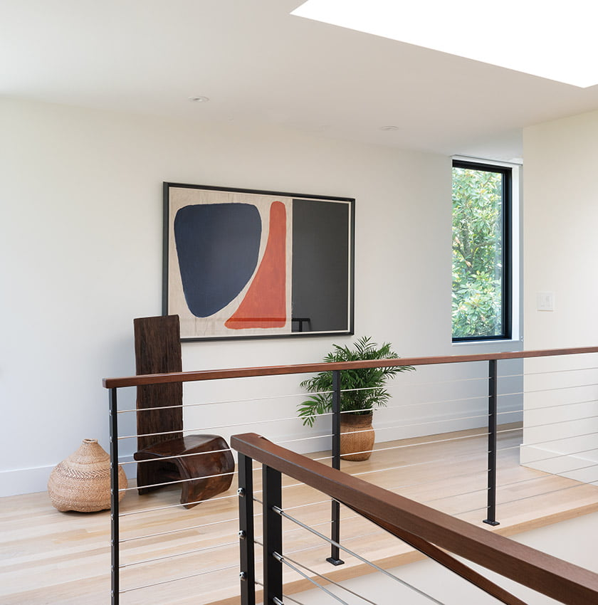 Steel cables and mahogany rails on the staircase reflect warmth and contemporary flair.