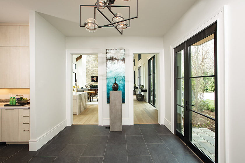 A colorful canvas in shades of blue hangs between doorways in a secondary entry.