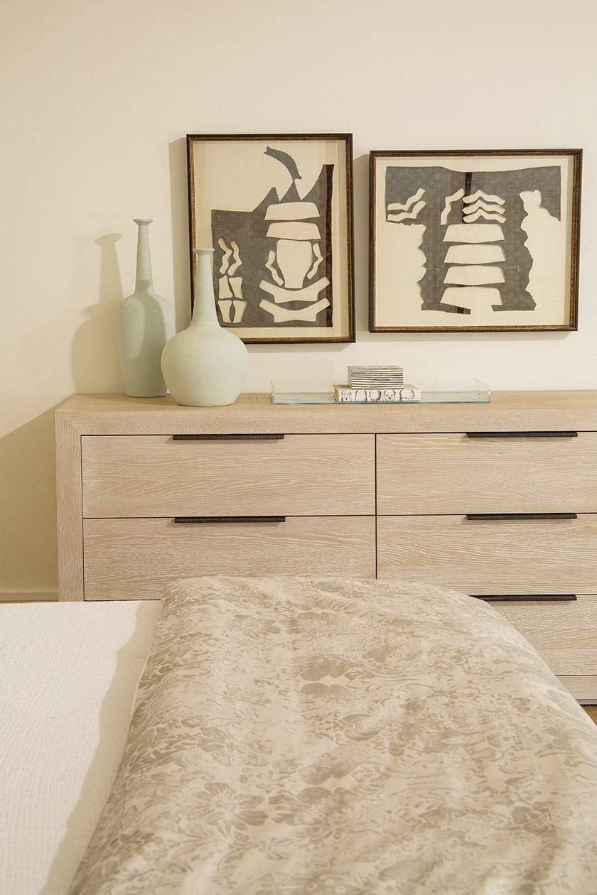 A Universal Furniture dresser is paired with framed antique Louis Vuitton purse patterns.