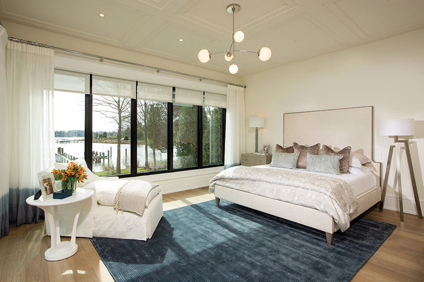 Water views inspired the blue Jaipur rug In the owners' suite, which contrasts with the white-on-white furnishings.
