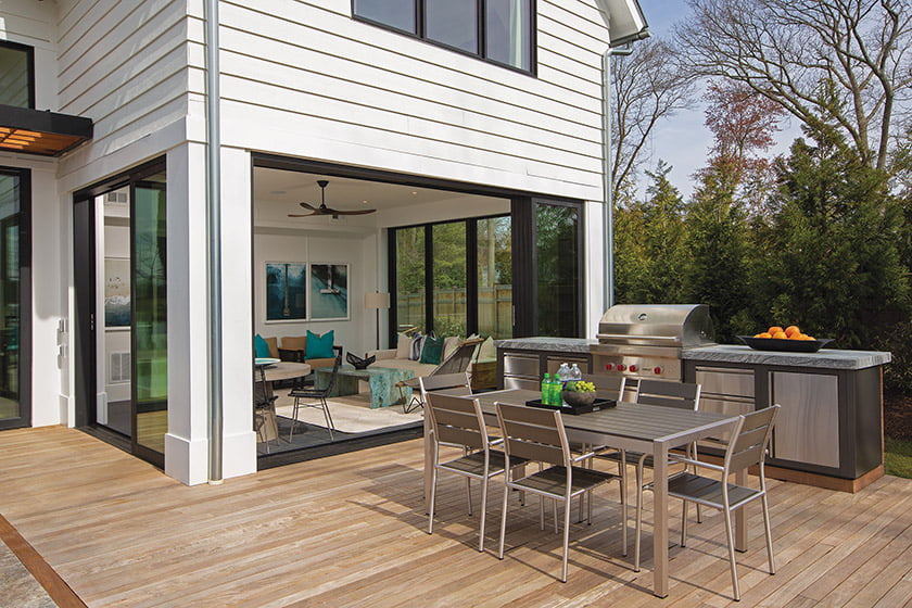 Sliders create an opening between the sunroom and the outdoor dining area