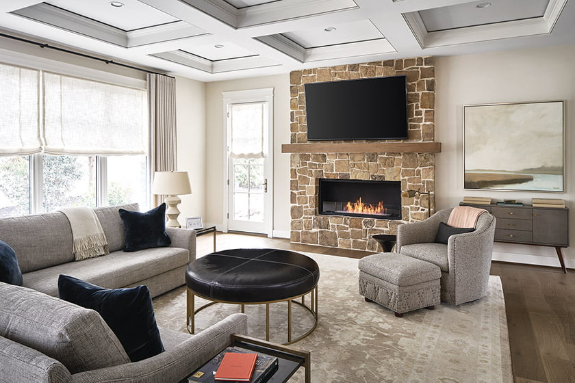 The family room's fireplace wall juxtaposes natural stone with sleek, linear styling.