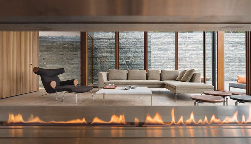 In the formal sitting area, a custom fireplace warms a B&B Italia sofa