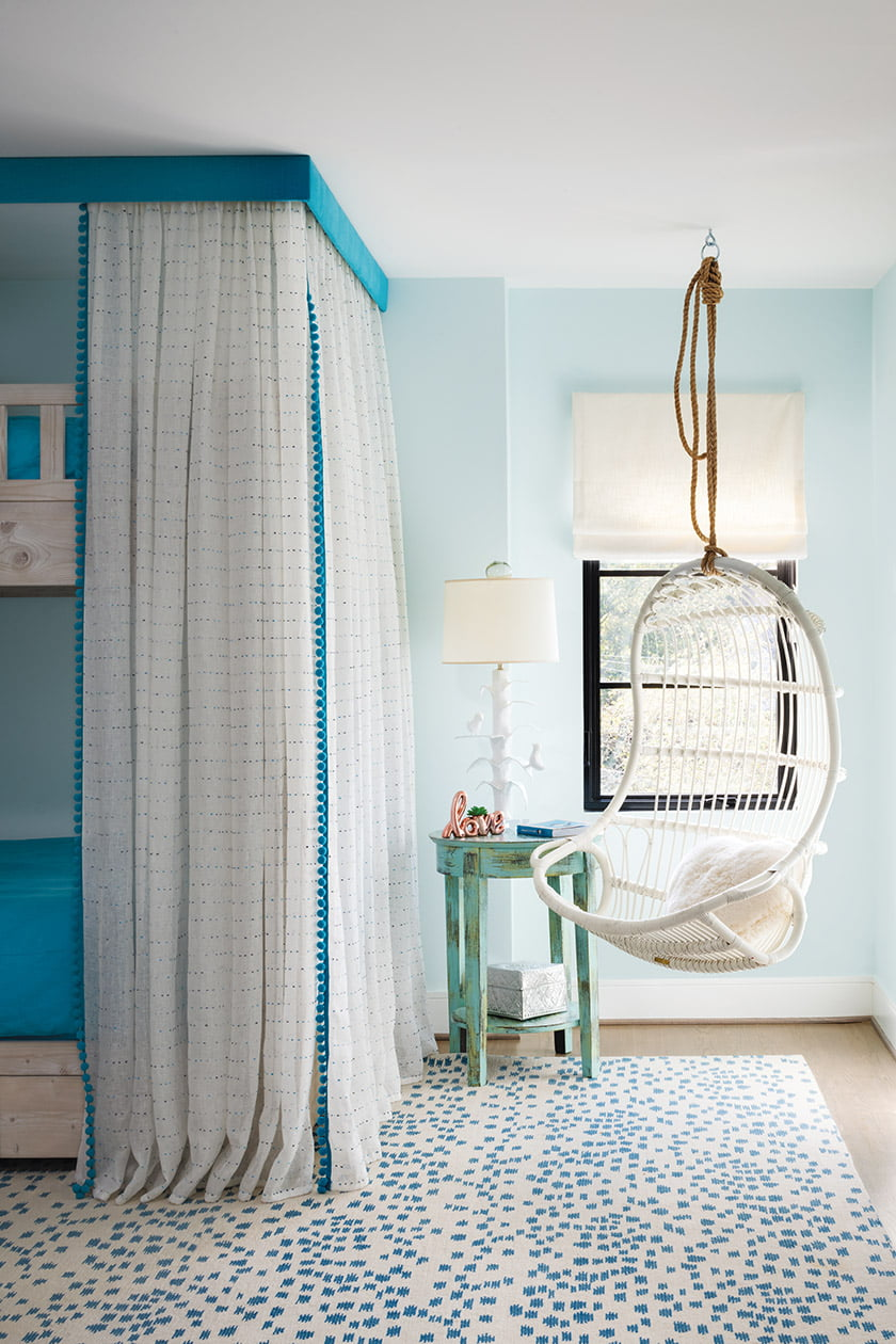 Serena & Lily hanging chair; Kathryn Ireland sheers and Romo pompom trim in child bedroom