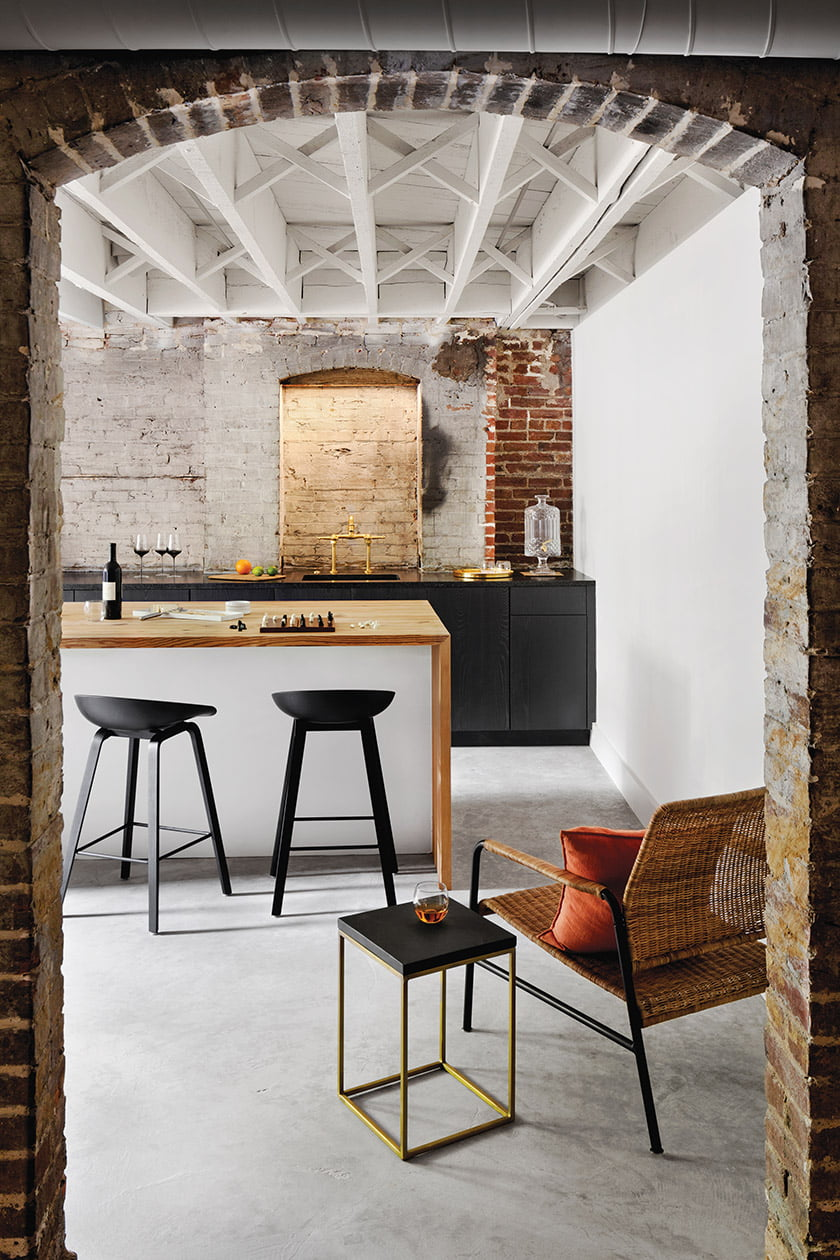 Exposed raw brick and ceiling joists with clean-lined ash bar cabinets
