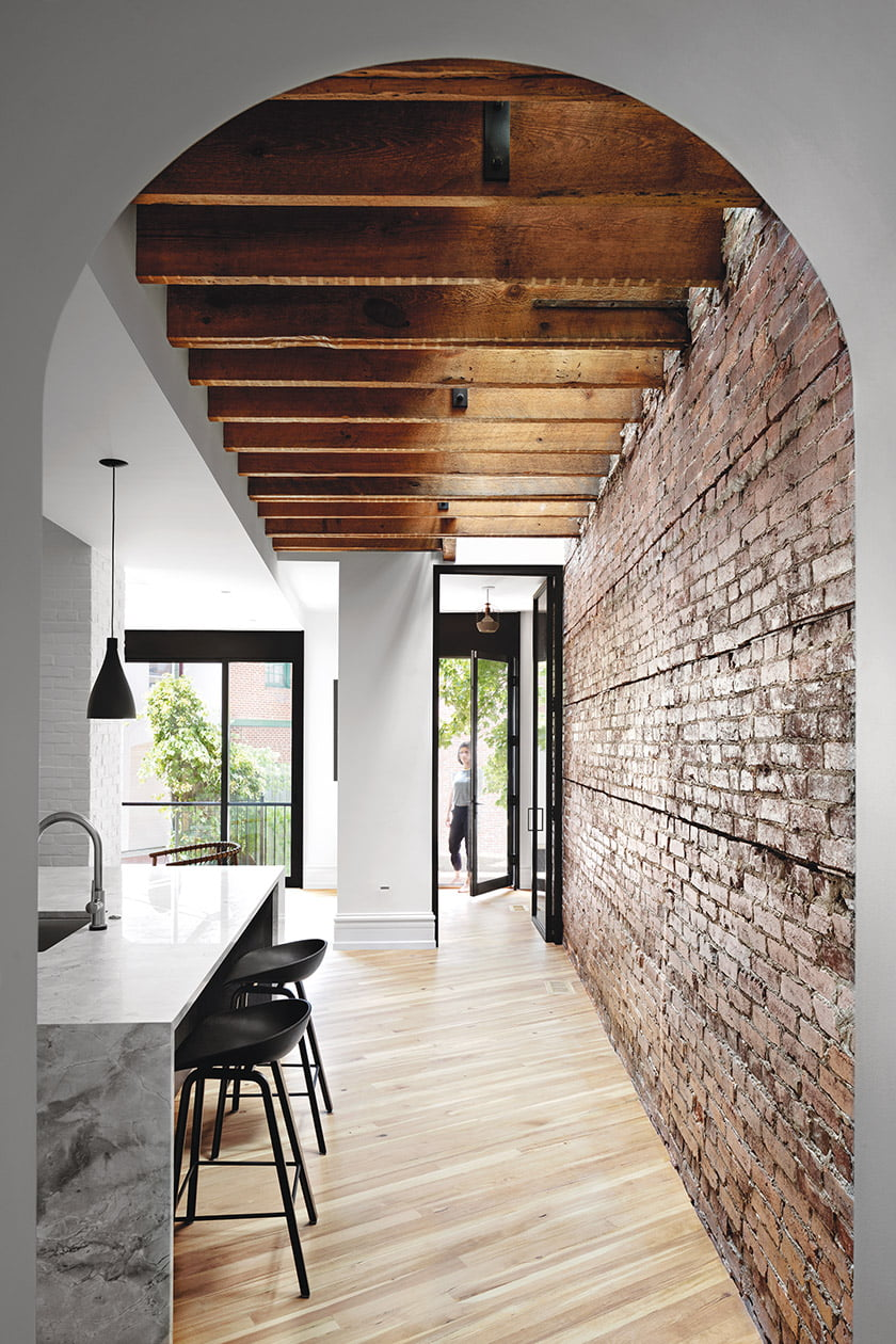 Exposed ceiling joists where glass-and-metal doors lead to the backyard