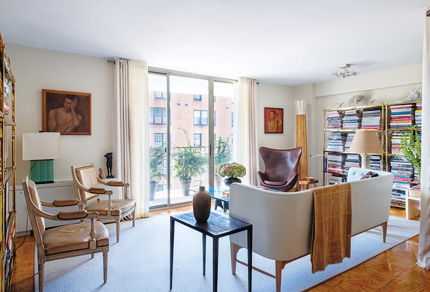 Living area with sliding balcony doors framed in Kravet drapery is anchored by rug from Bloomsburg