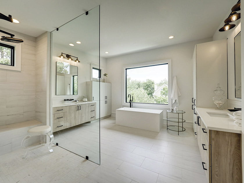 Large glass partition borders the shower with polished porcelain tiled floor
