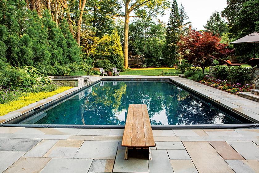 宾夕法尼亚石板边框泳池与鲜花和郁郁葱葱的灌木丛