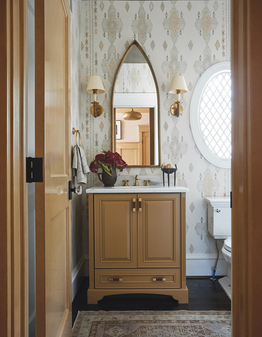 Powder room with stone countertop, custom Moroccan-style window grate and Kit Kemp wallpaper
