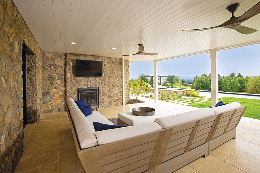Lower level covered porch bordered by stone foundation walls