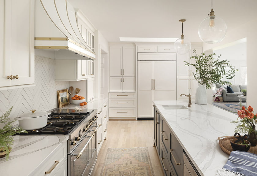 Kitchen custom cabinetry and range hood trimmed in brass