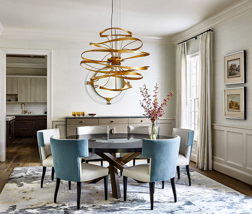 Dining room table with brass Corbett chandelier above