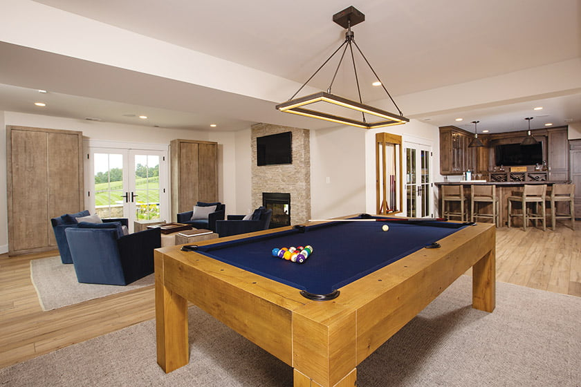 Billiards and TV area with rustic wood accents and built-in storage