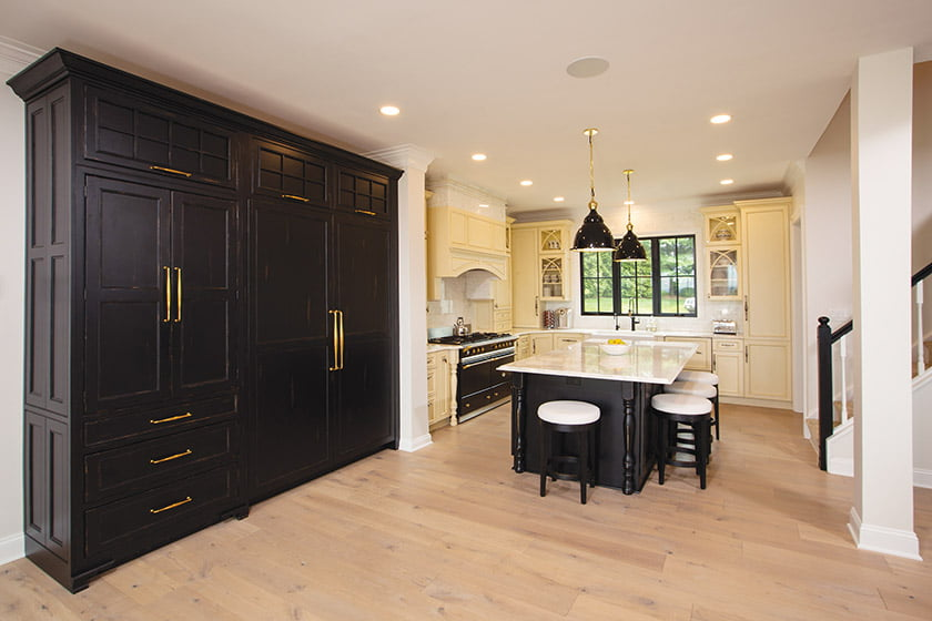 Kitchen with black-painted refrigerator and freezer panels