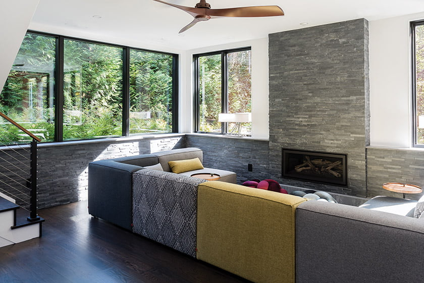 Lower-level lounging space anchored by a ledgerstone fireplace