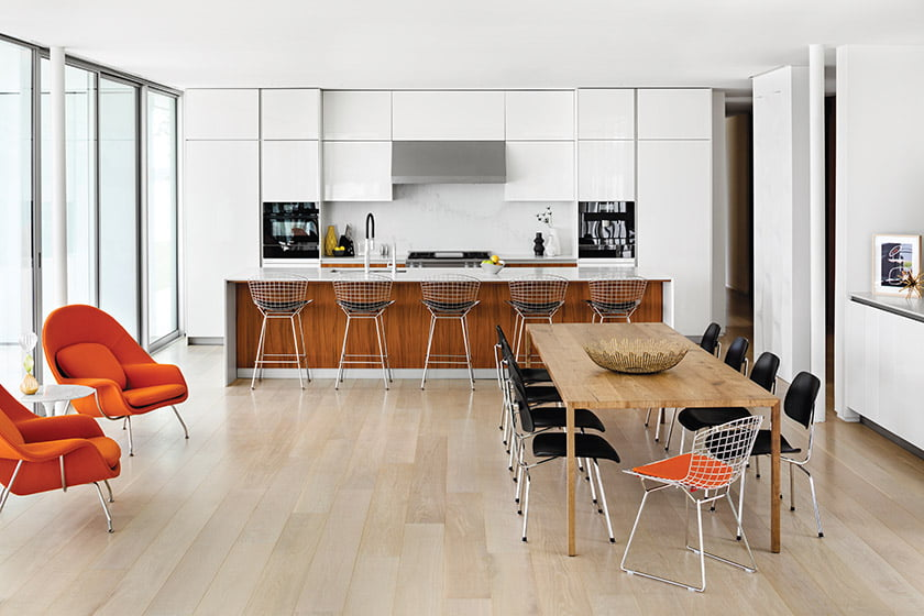 Open kitchen features white-lacquer and walnut cabinetry from Snaidero