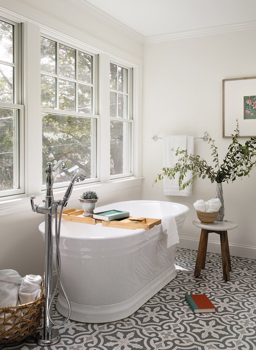 Patterned encaustic tile and sculptural soaking tub in owners bath
