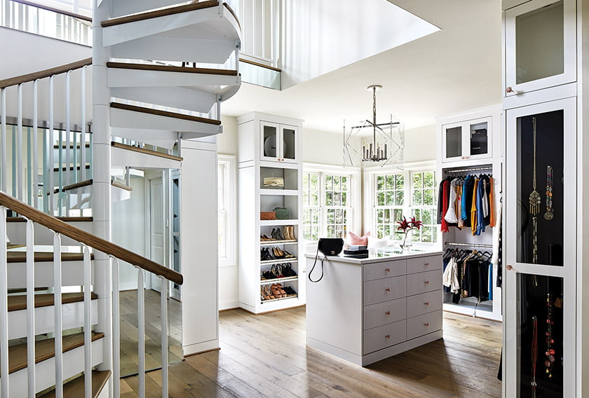 Owners closet by Tailored Living has spiral stairs that leads to loft space in attic