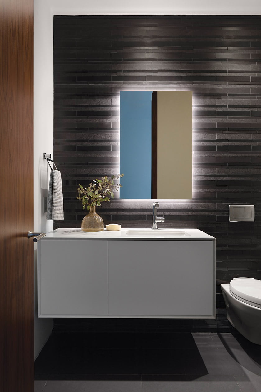 Powder room features Daltile's Unity porcelain tile in Nero and Grohe faucet