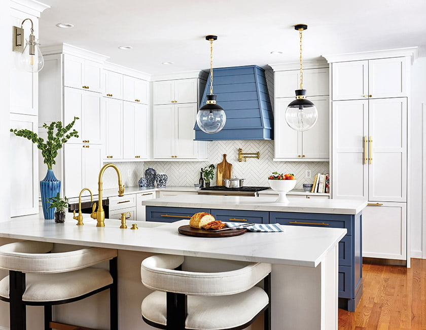 Pops of blue enliven a chic kitchen with crisp-white cabinets and a custom hood as a focal point.