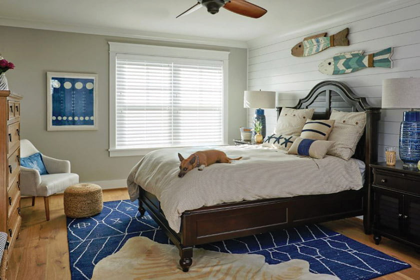 An inviting guestroom layers new and vintage elements, nautical motifs and blue accents.