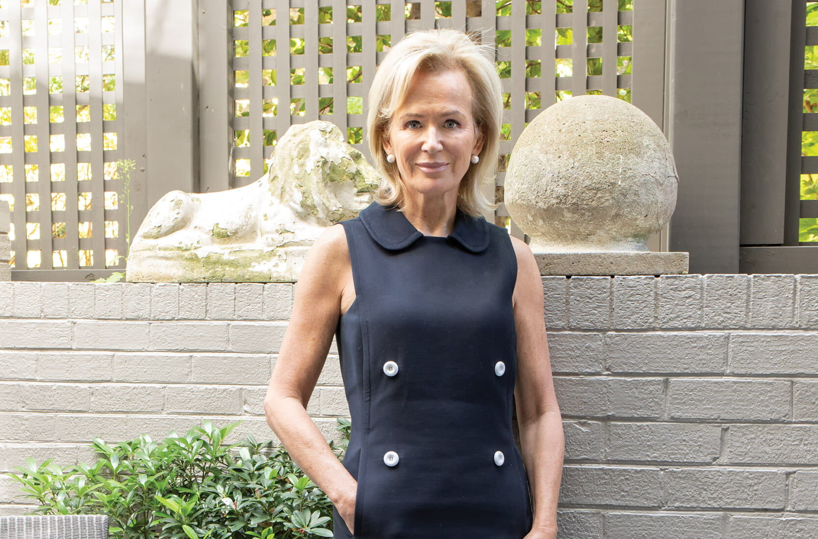 Fabiola Martens beside antique garden sculptures and a chair from JANUS et Cie on the patio outside bedroom.