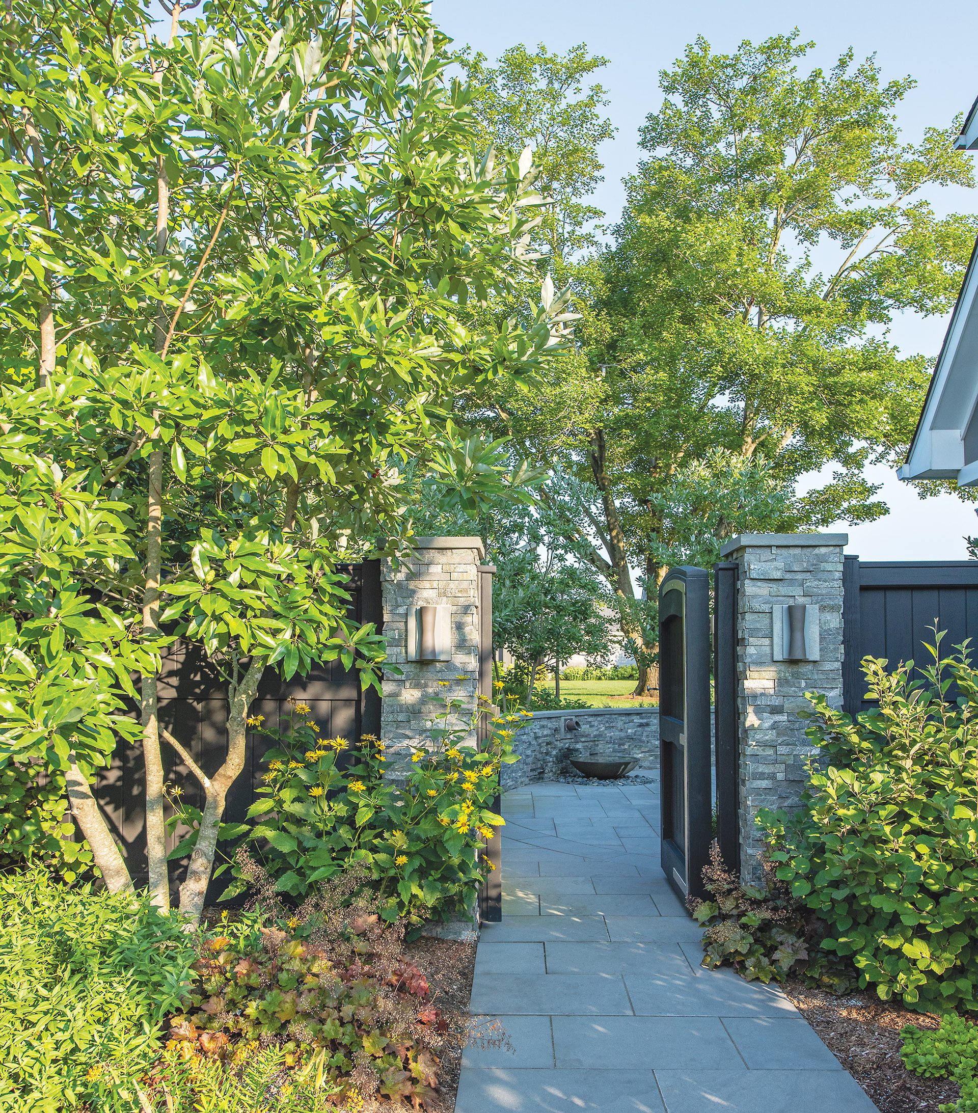 Black-stained garden gate, stone-rimmed courtyard, and concrete-and-copper water feature from Lunaform.