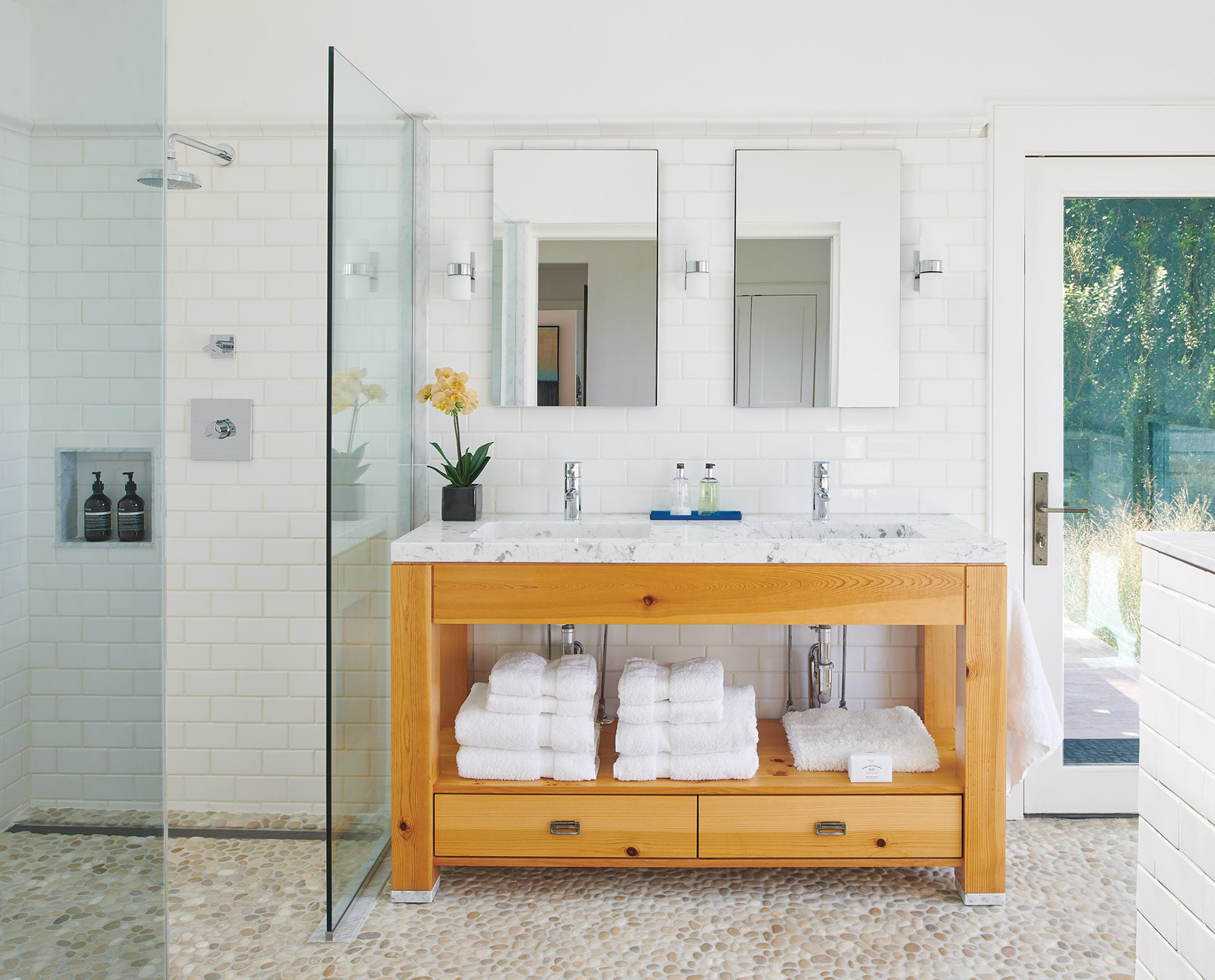 Owners' bathroom, marble-topped, knotty-pine vanity and pebbled flooring from Ann Sacks.