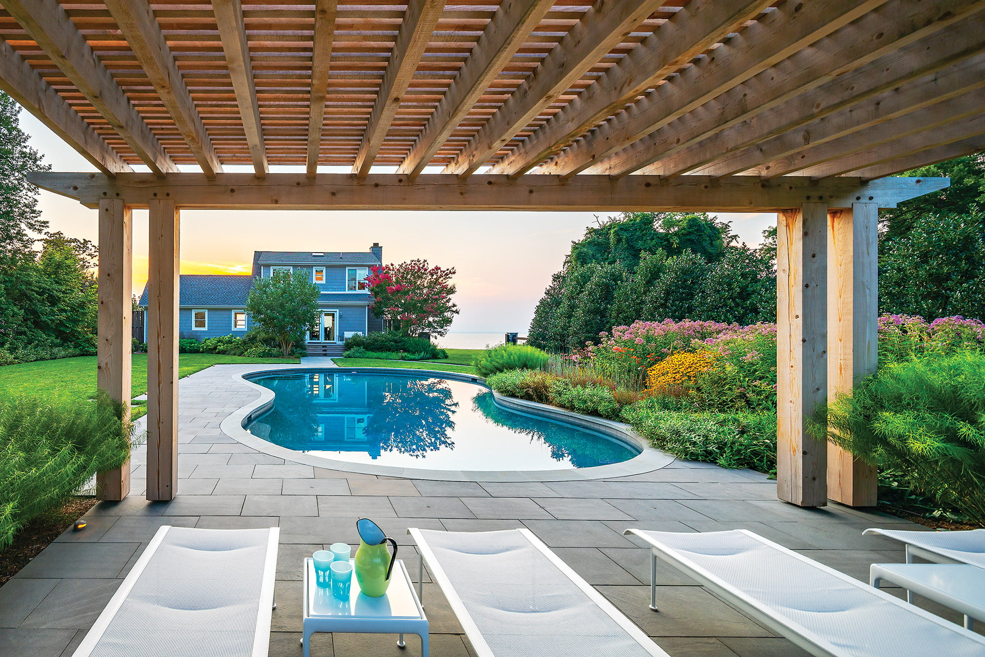 Pergola lounge area by pool, house and bay.