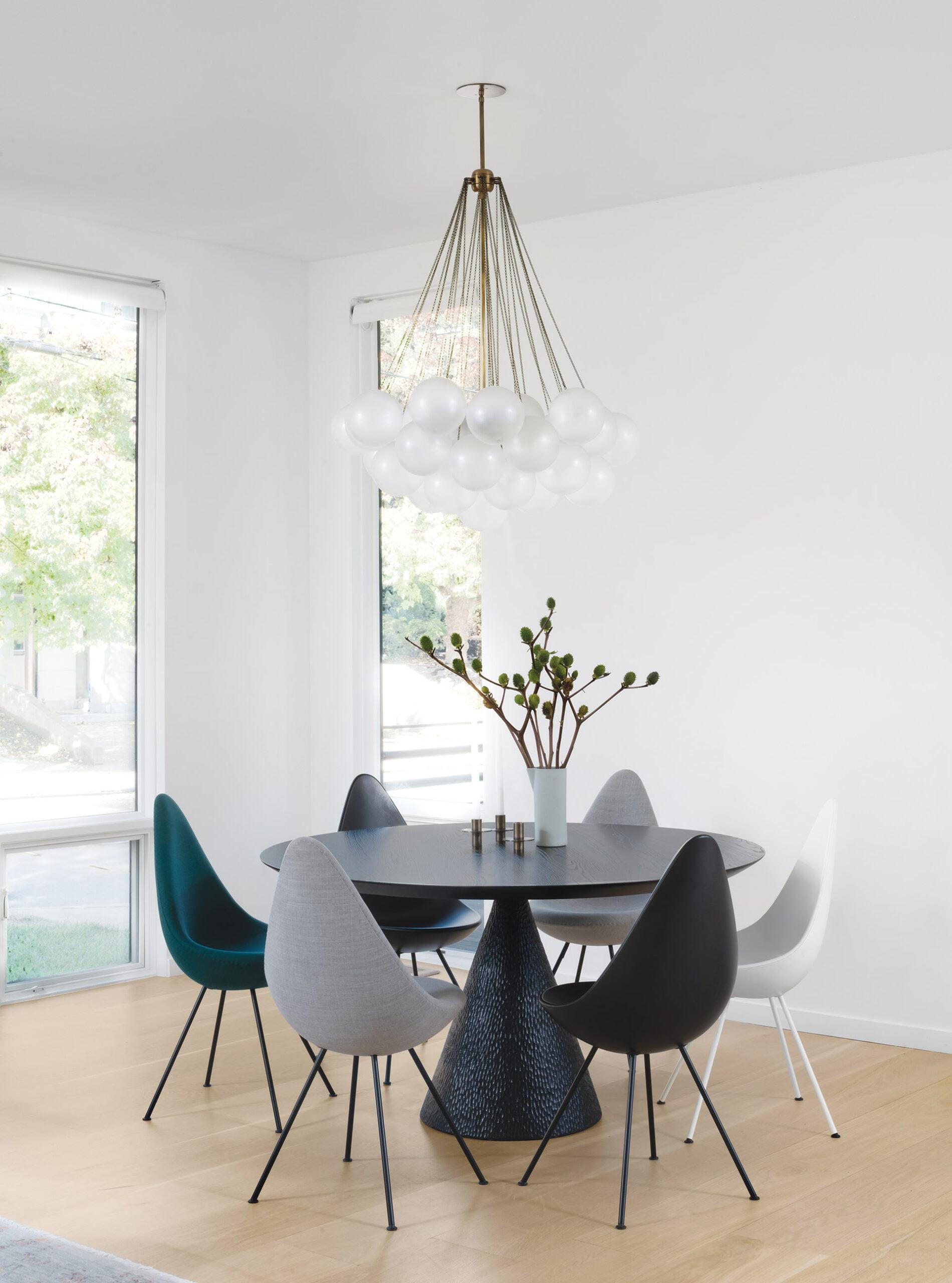 餐厅桌子和Arne Jacobsen Drop椅子在斯堪的纳维亚家具的kvadrat织物中布满;一个设备枝形吊灯