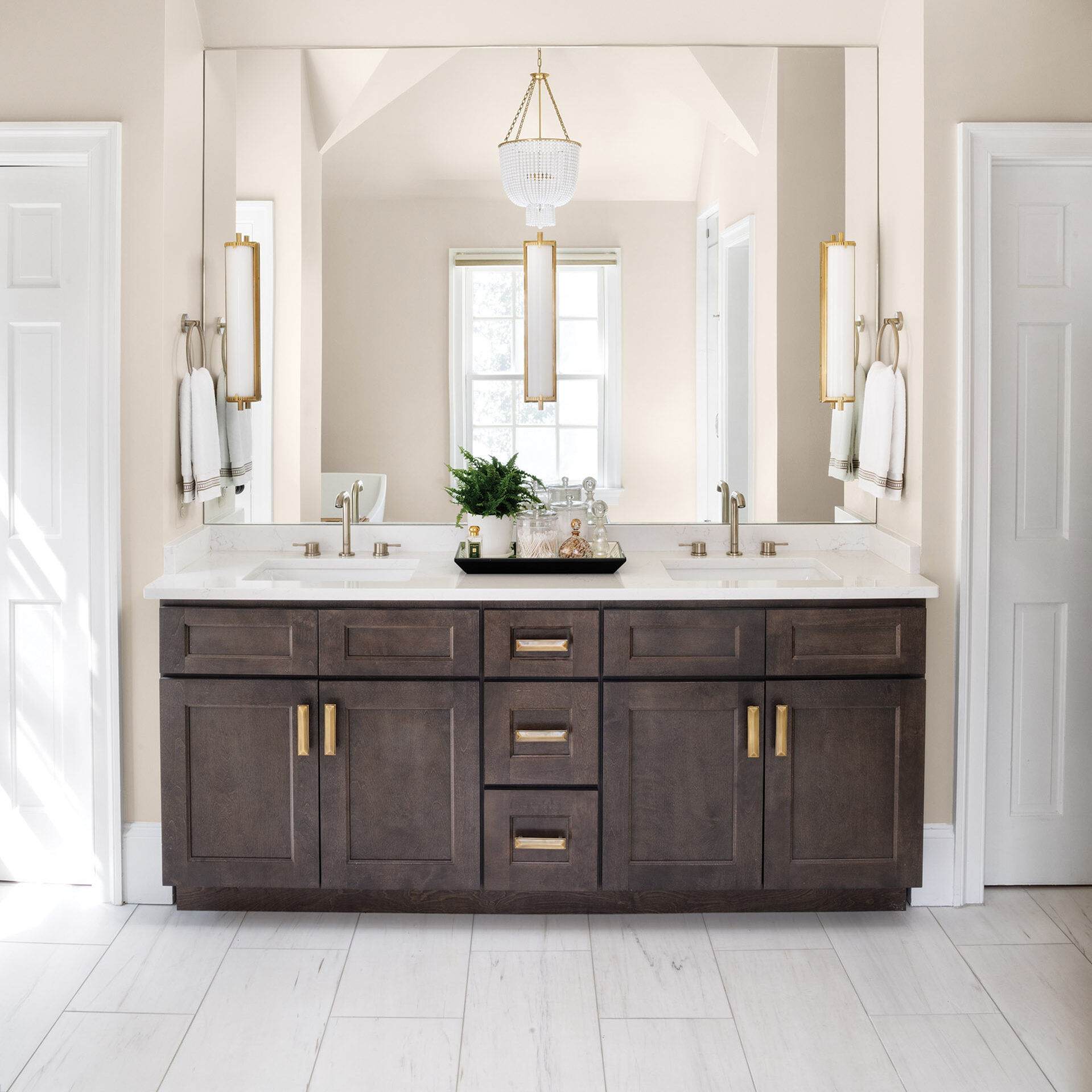 Dark-stained wood double vanity topped with quartz countertop.
