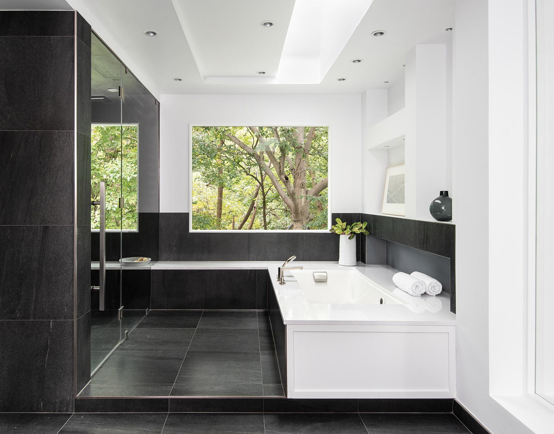 墙壁和加热地板上的白色口音和木炭灰色瓷砖