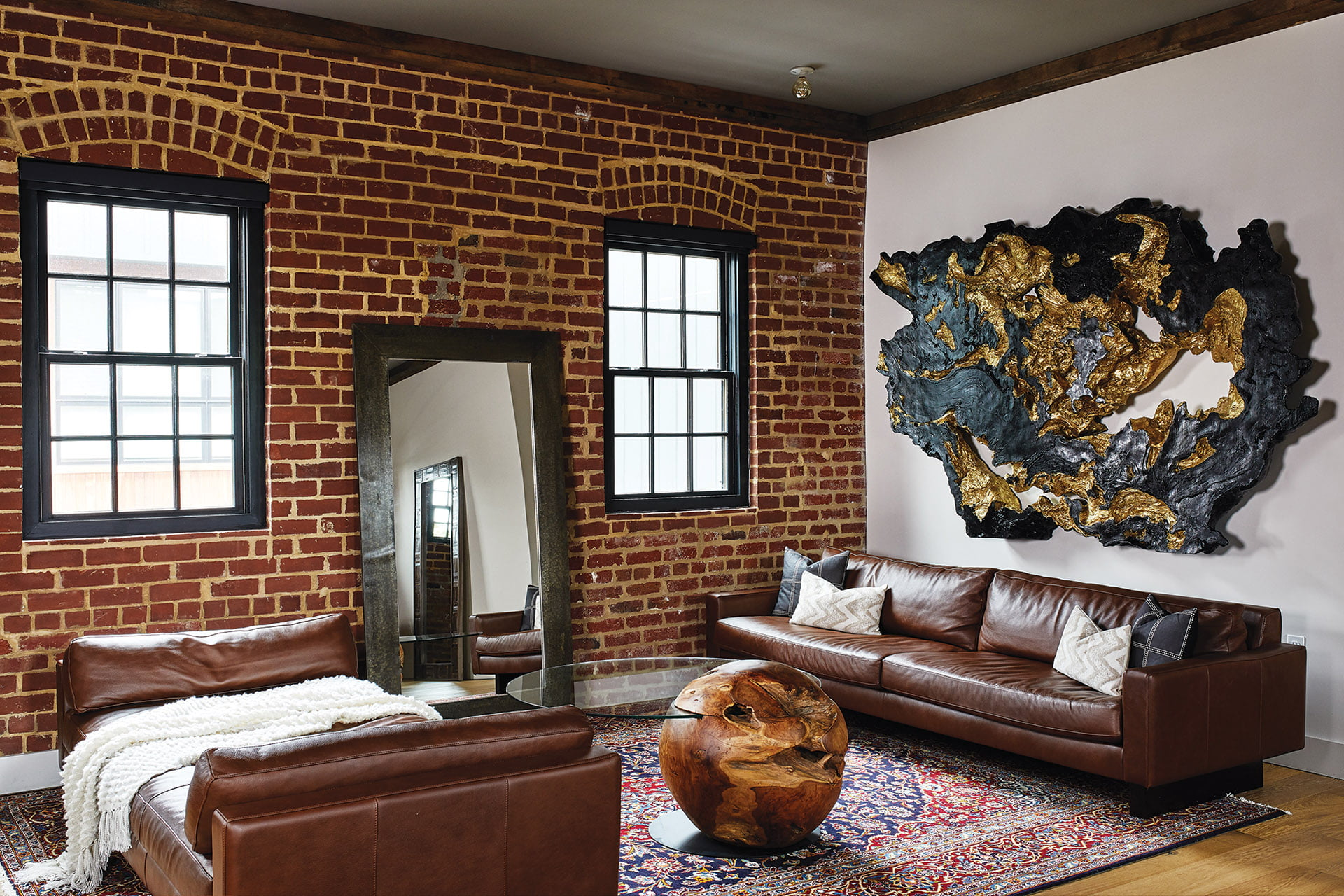 Living room features Room & Board leather sofas and a three-dimensional resin wall sculpture.