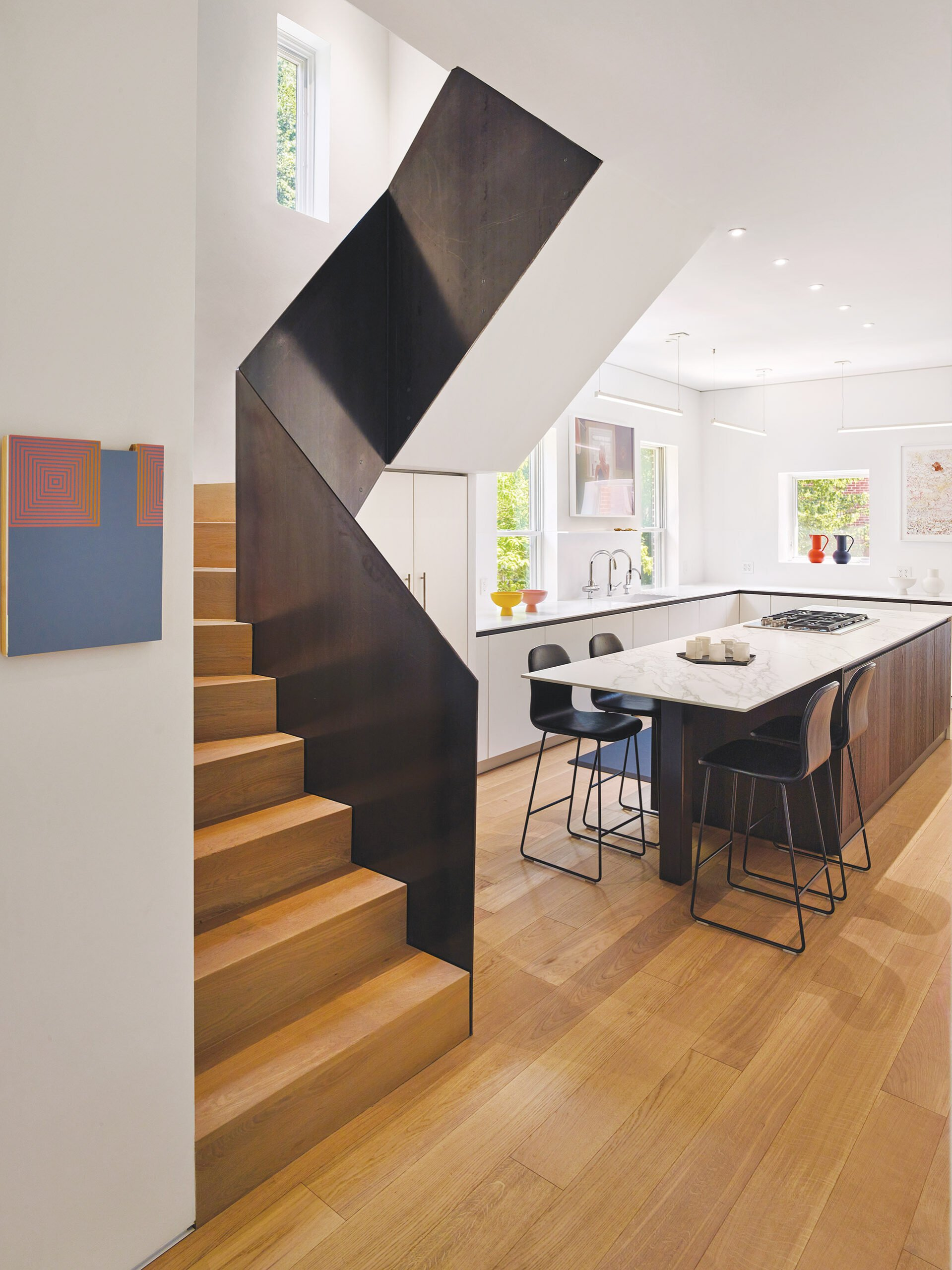 Staircase defined by welded-steel plates. Kitchen by Contemporaria, Cesar cabinetry and anigre wood island.