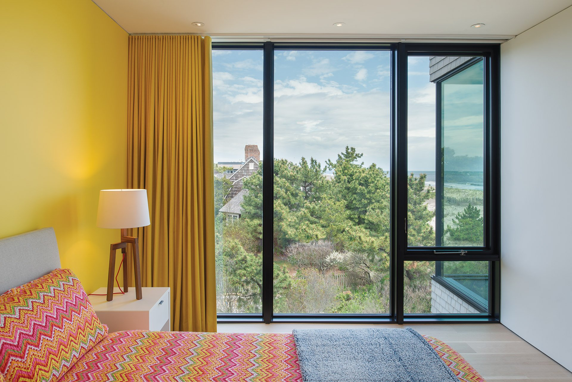 Sunny walls and drapery animate a bedroom.