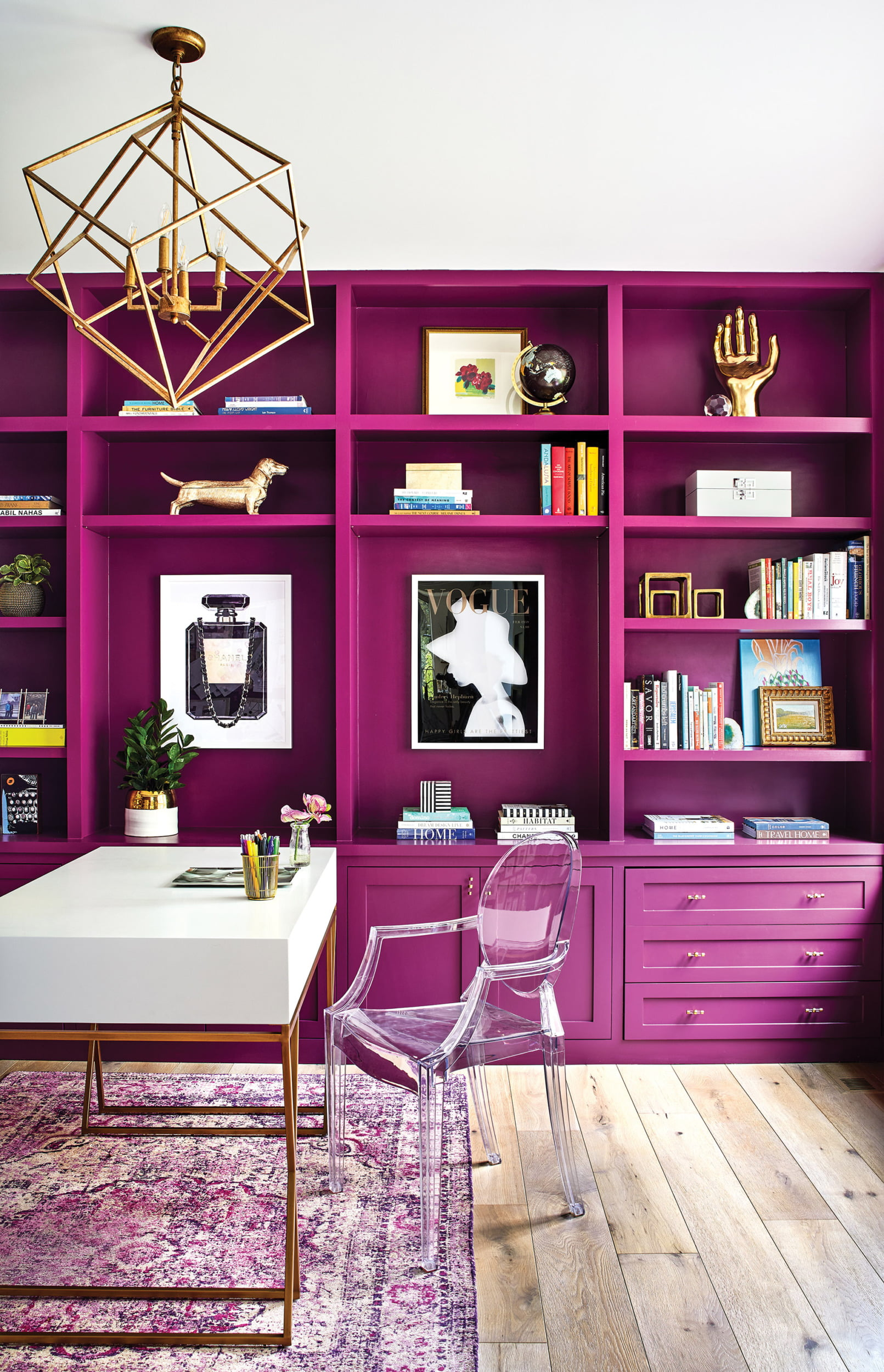Bright-pink home office features chic writing desk and acrylic chair atop a colorful rug.