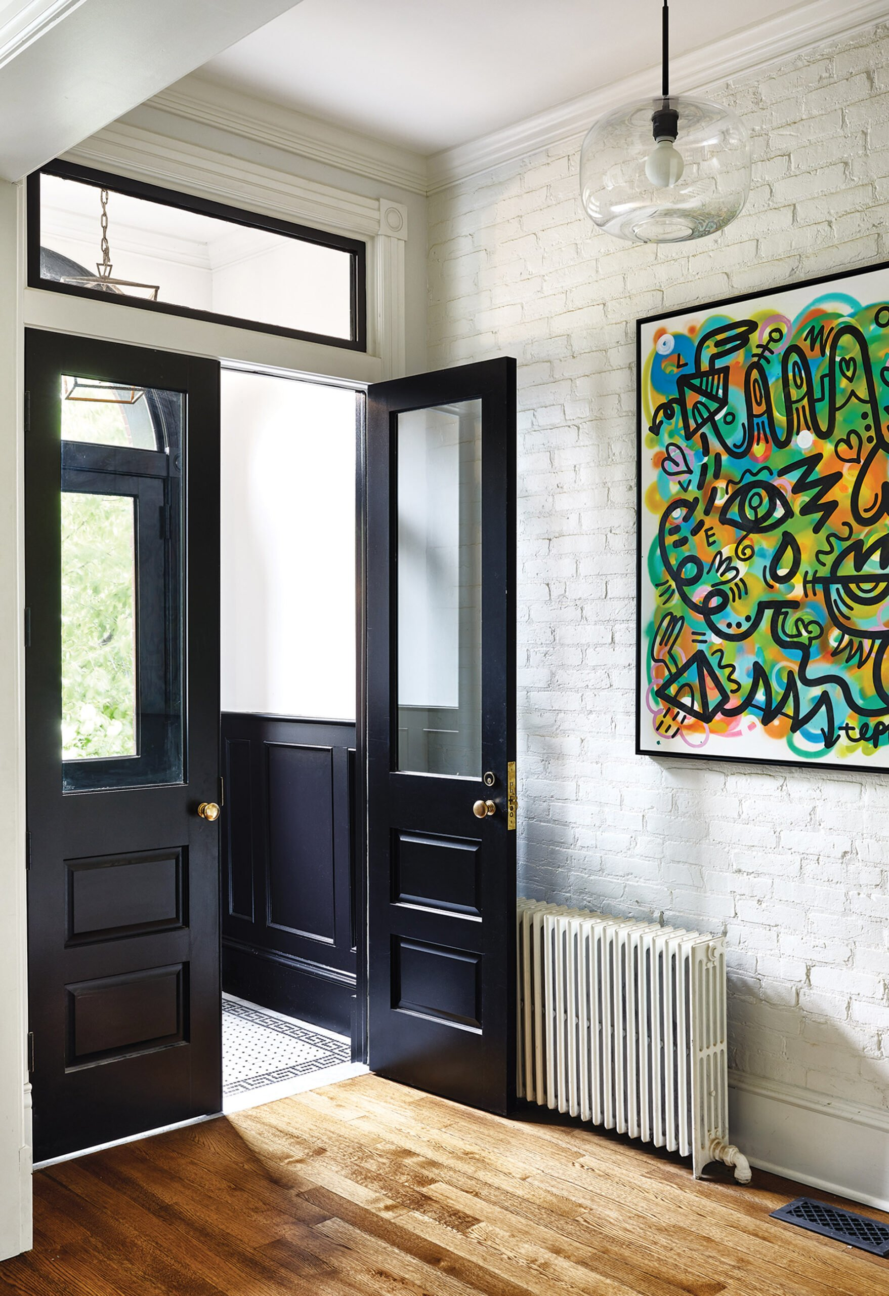 Exposed-brick wall painted white with clear-glass doors in a vestibule.