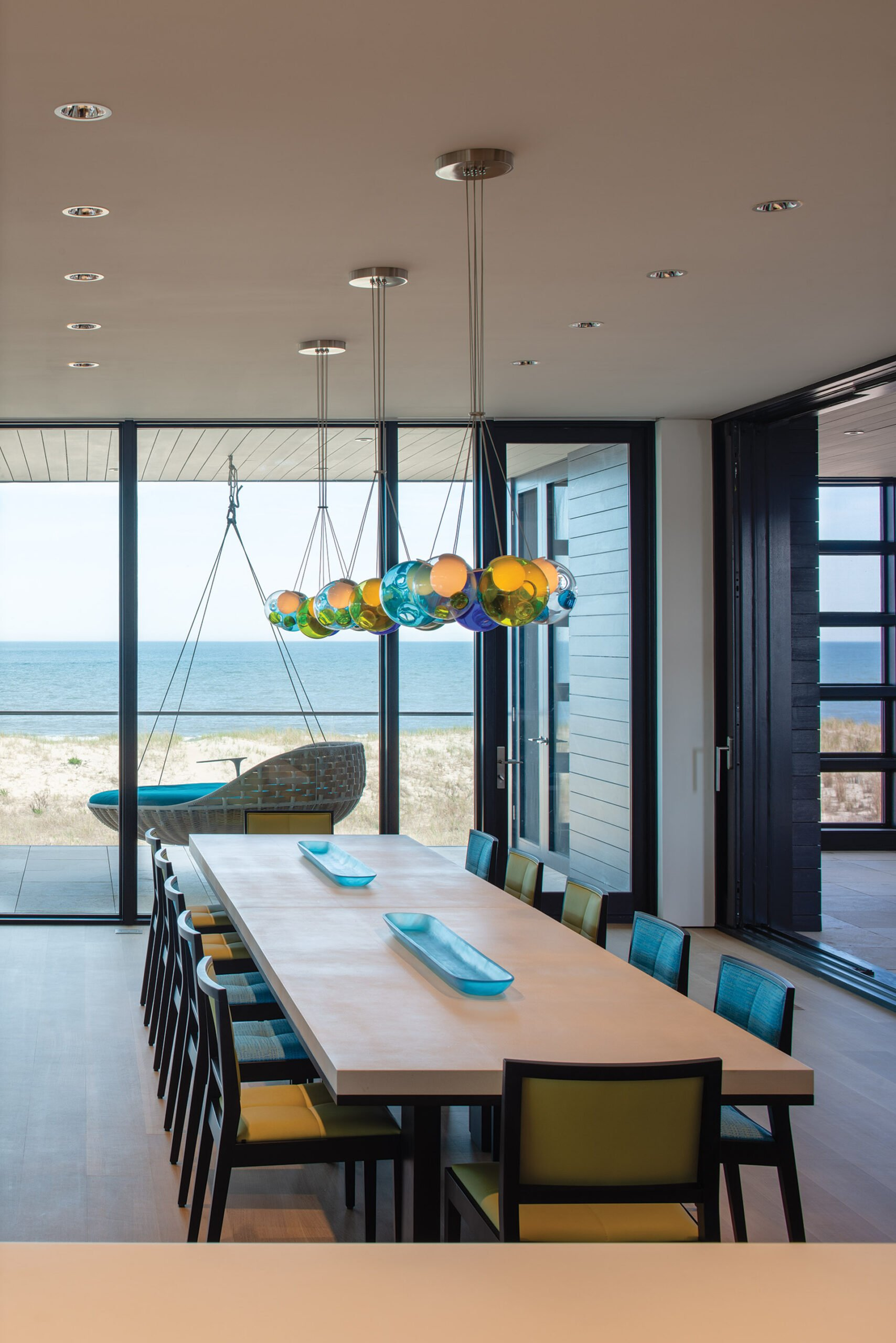 Bocci chandeliers hang above a pair of cast-resin Liaigre dining tables