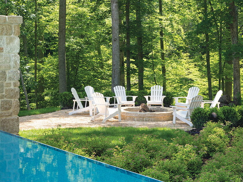 Spirea and hydrangea shrubs lead from the pool to a circle of Adirondack chairs around the woodland fire pit.