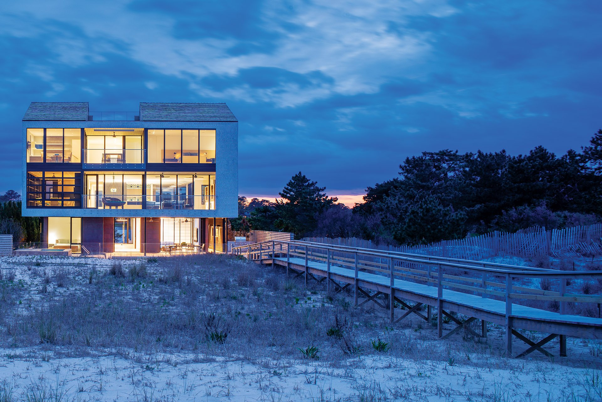 Beach home glass-rimmed upper levels cantilever over the pool terrace