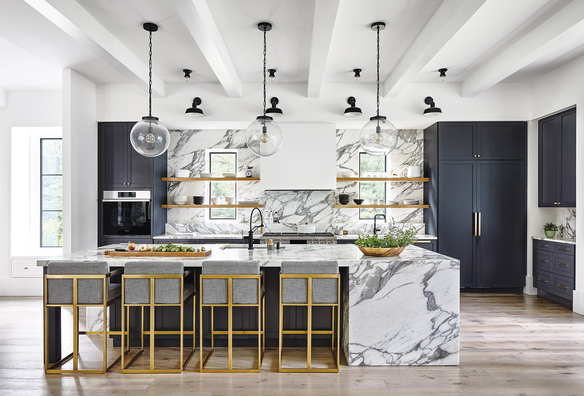Calacatta Vagli marble surfaces with globe pendants above the island.