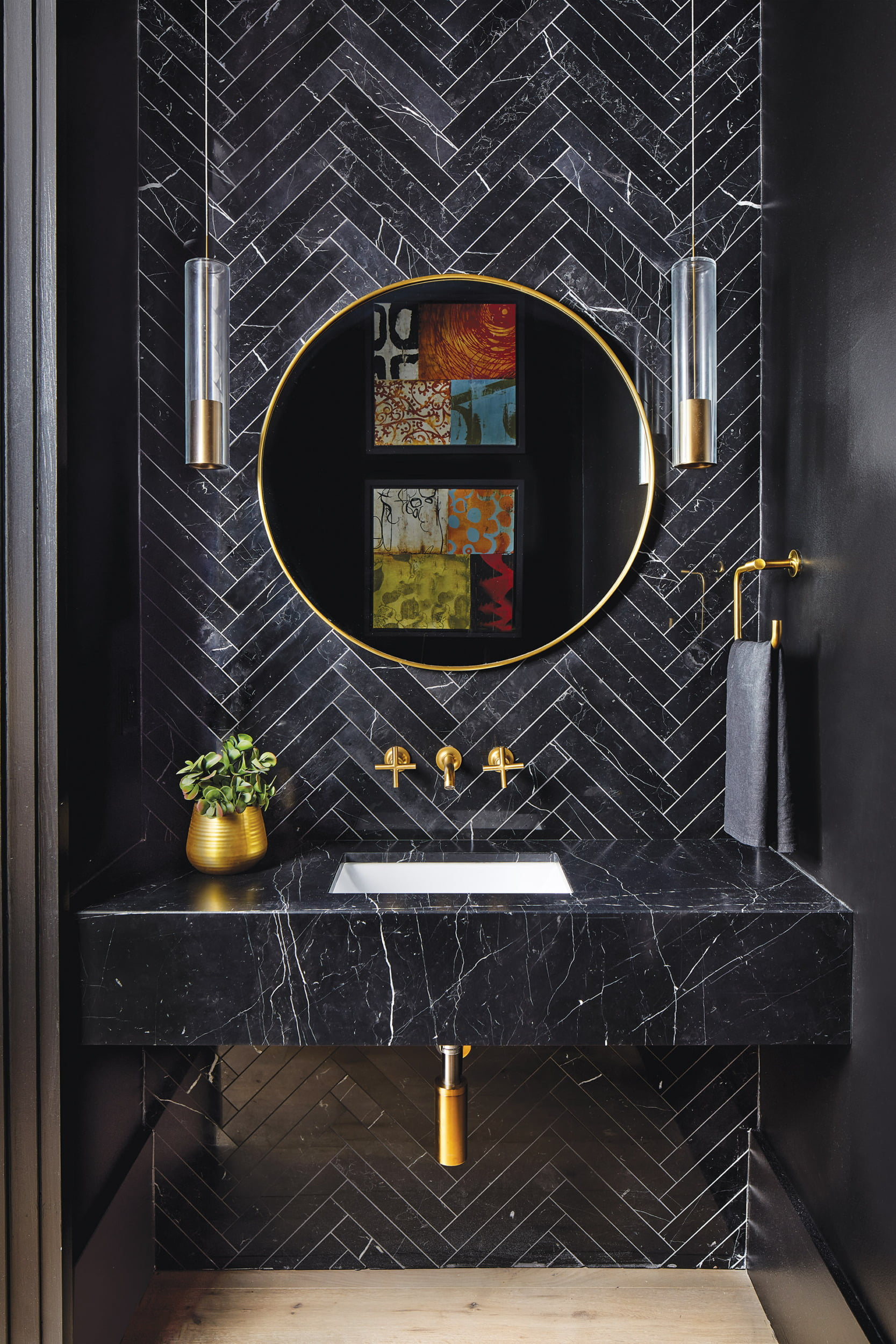 Powder room offsets Nero Marquina marble surfaces with gold accents and RH pendants.