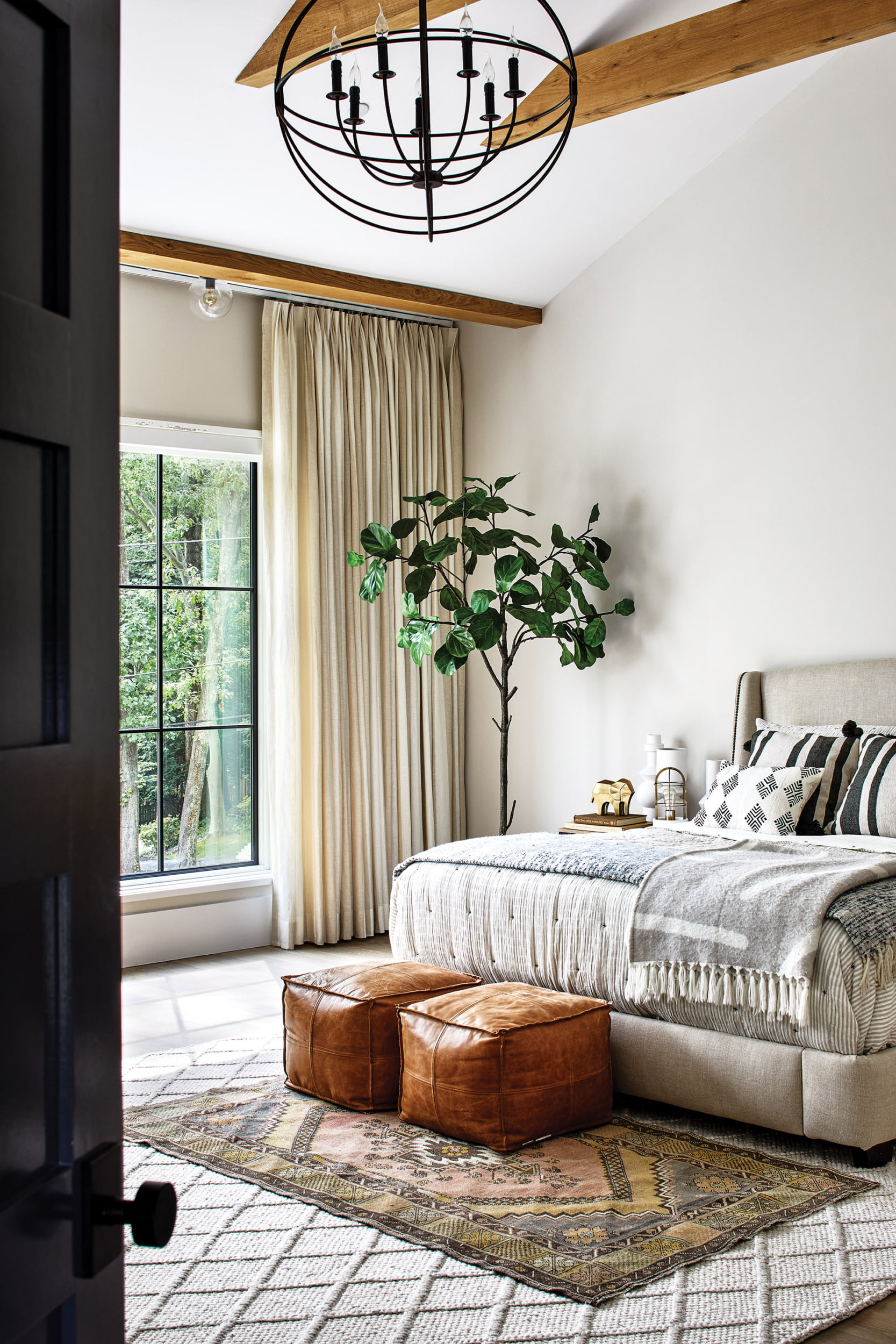 Off-white walls, warm oak accents and custom bedding in owners bedroom