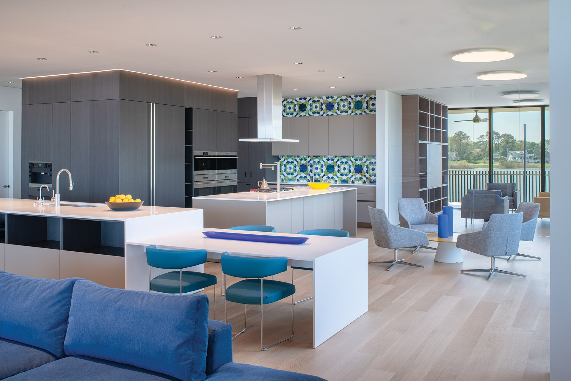 Dual-height island separates the living area and kitchen featuring Boffi cabinetry and a Zephyr hood