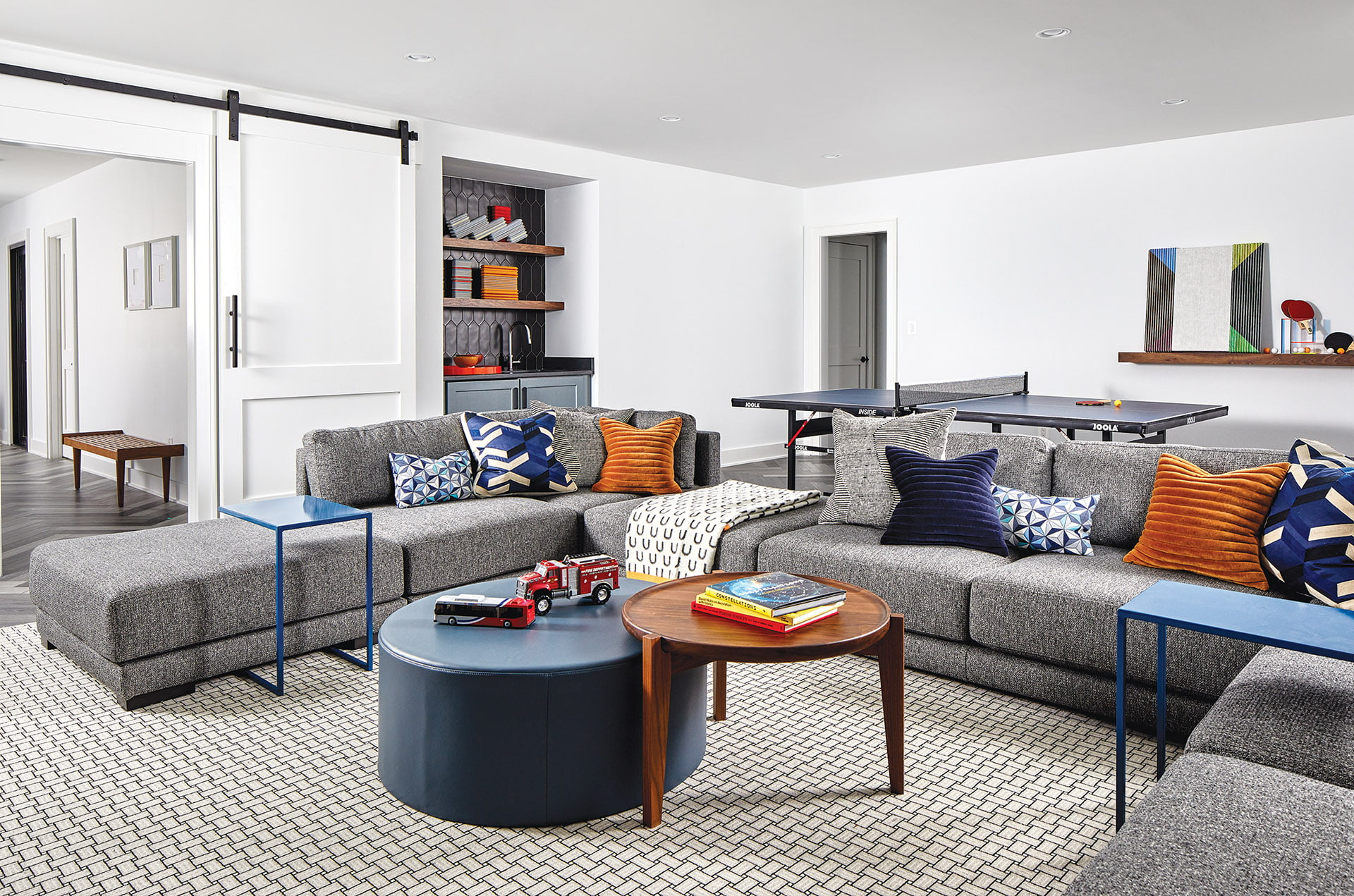 Play area with sectional sofa, tables and ottoman from Room & Board